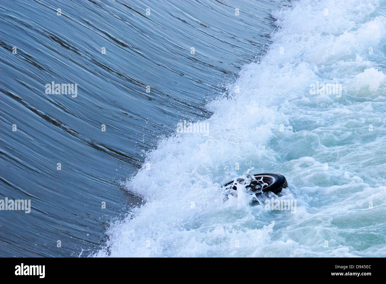 Rubber tire trapped in the powerful recirculating hydraulic wave (aka drowning machine) of a weir on the Bow River - Stock Image
