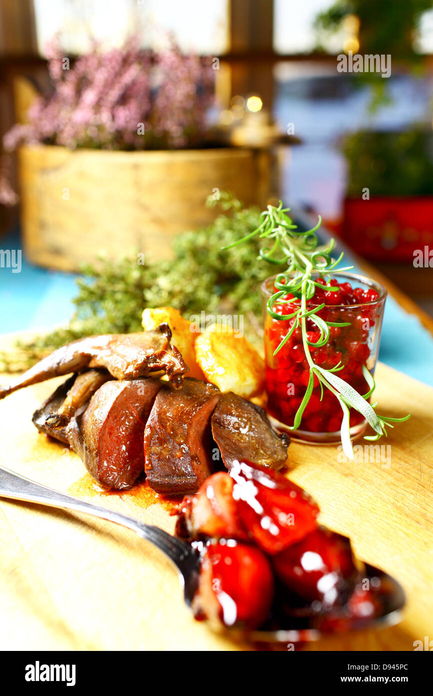 Grouse and lingonberry dish on cutting board - Stock Image