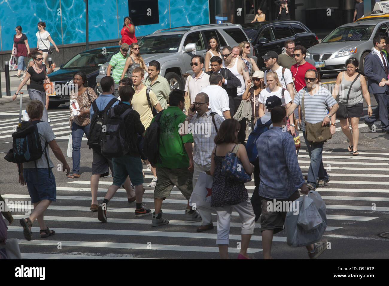 The corner of 42nd St. and 5th Avenue is always crowded with New Yorkers and tourists in midtown Manhattan. - Stock Image