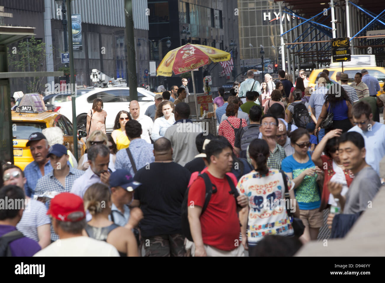 Crowds of tourists walk along 42nd St. by the NY Public library on a warm weekend in May. NYC - Stock Image