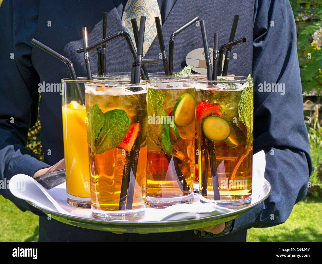 Waiter and summer drinks tray on alfresco luxury hotel garden terrace - Stock Image