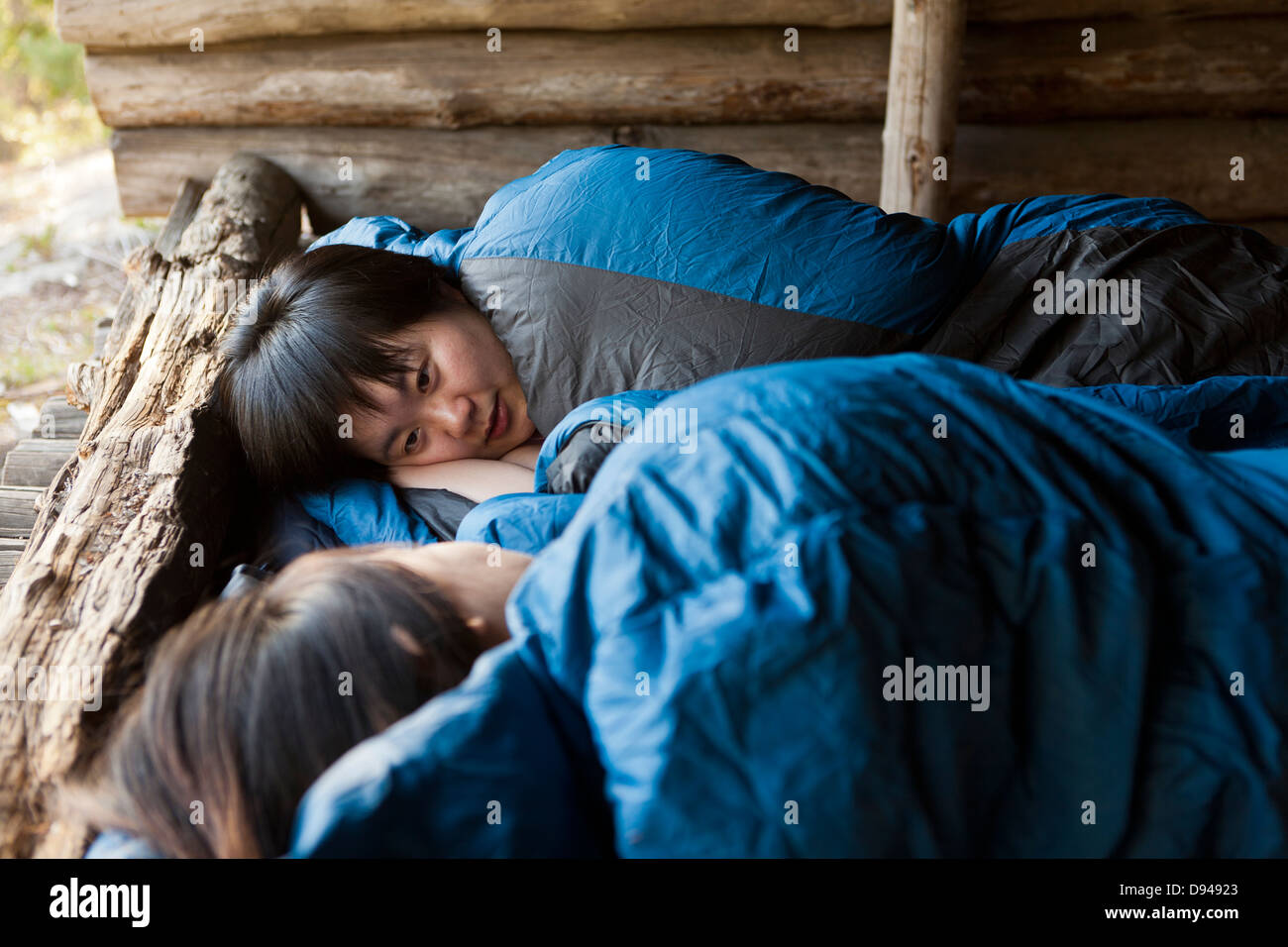 Two female tourists sleeping in shelter - Stock Image