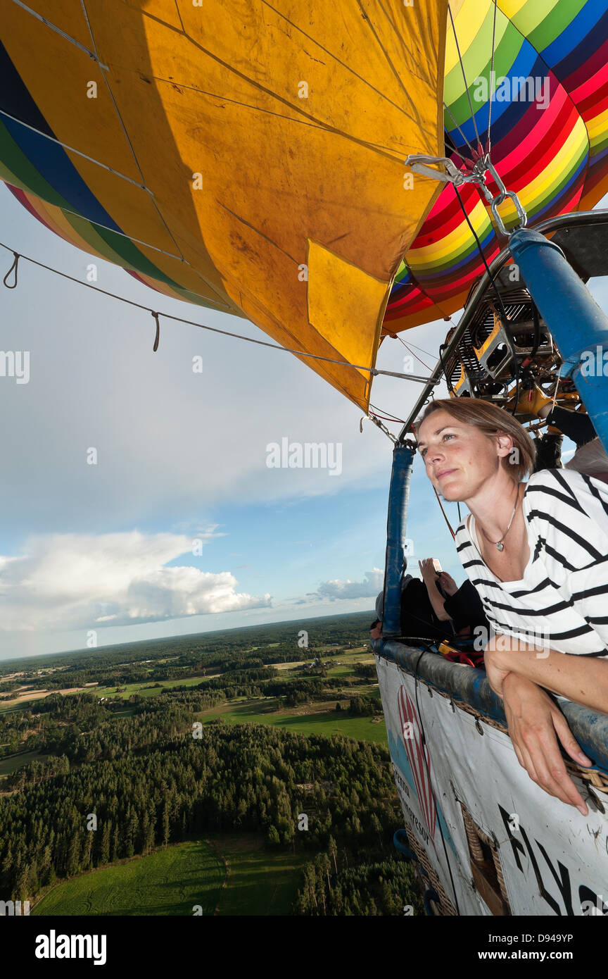 Woman flying in hot air balloon - Stock Image