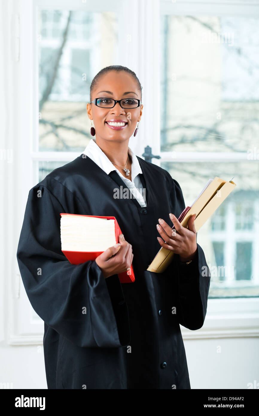 Young female lawyer working in her office with a typical law book and a file or dossier - Stock Image