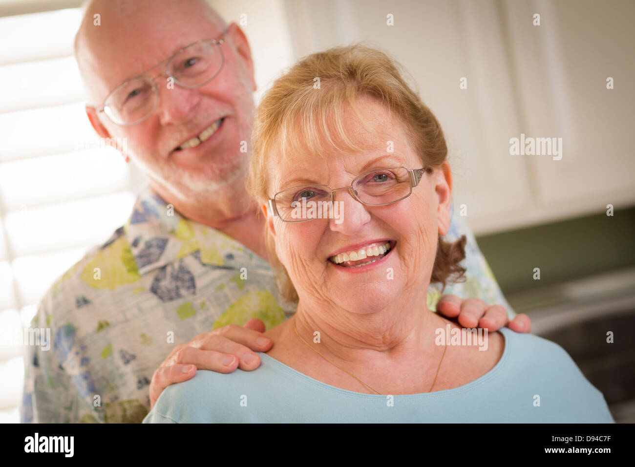Happy Caucasian Senior Couple Portrait Inside Kitchen. - Stock Image