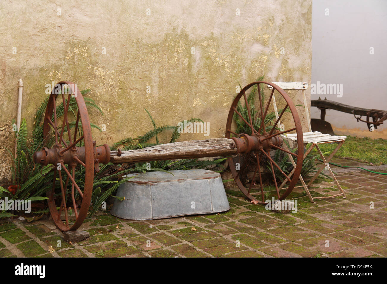 An old cart wheel sits in the garden of a home in Colonia de Stock ...