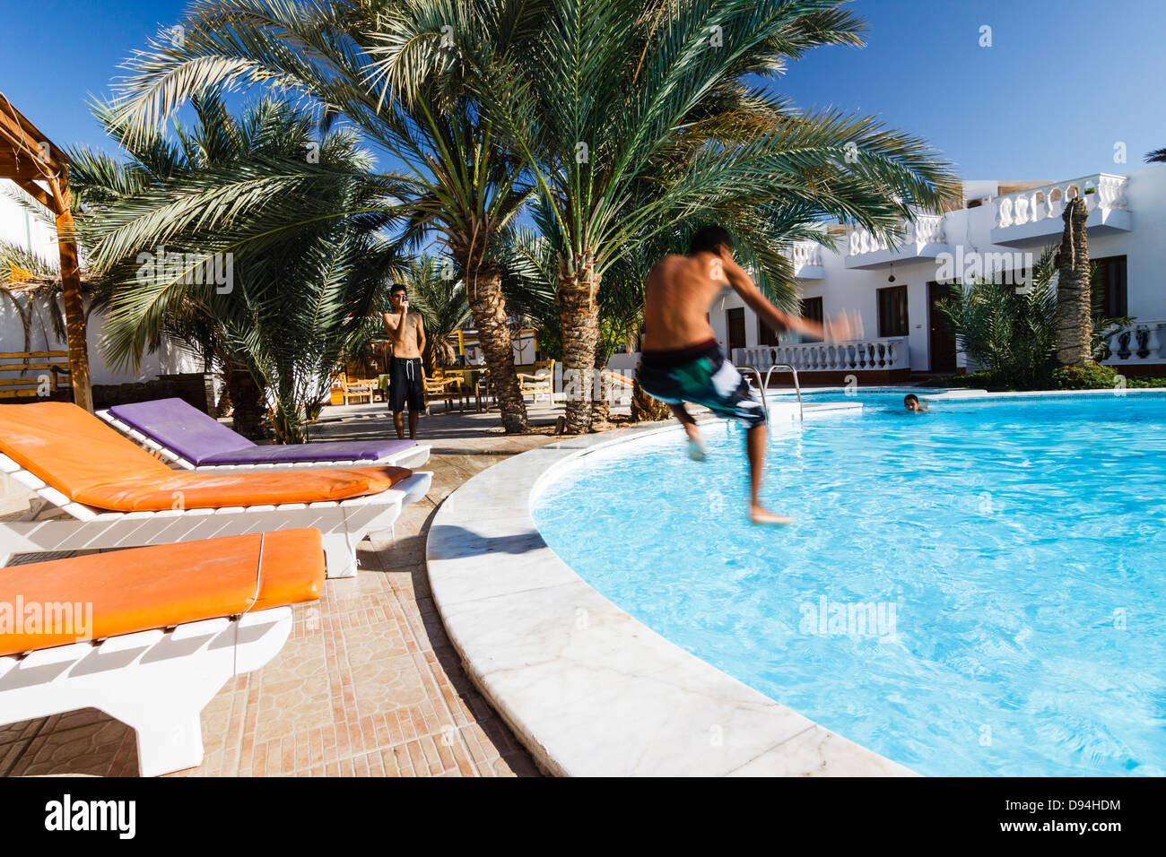 Jumping on the swimming pool of a tourist resort in Dahab, Egypt - Stock Image