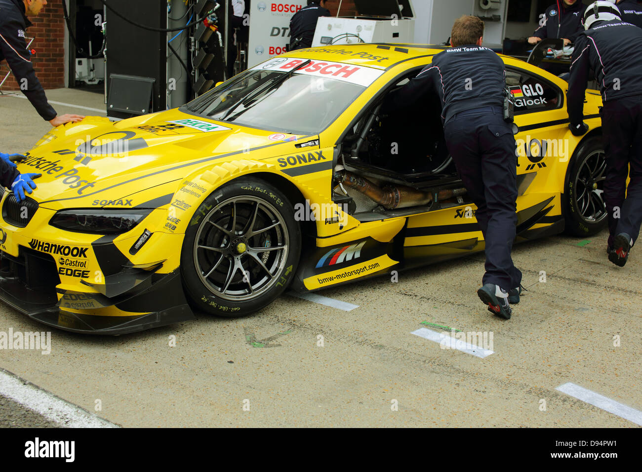 German DTM Touring Car Series, Brands Hatch Circuit. Pit crew working on the car. - Stock Image