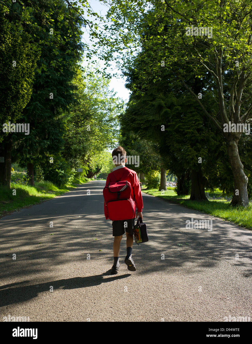 a young boy walks to school - Stock Image