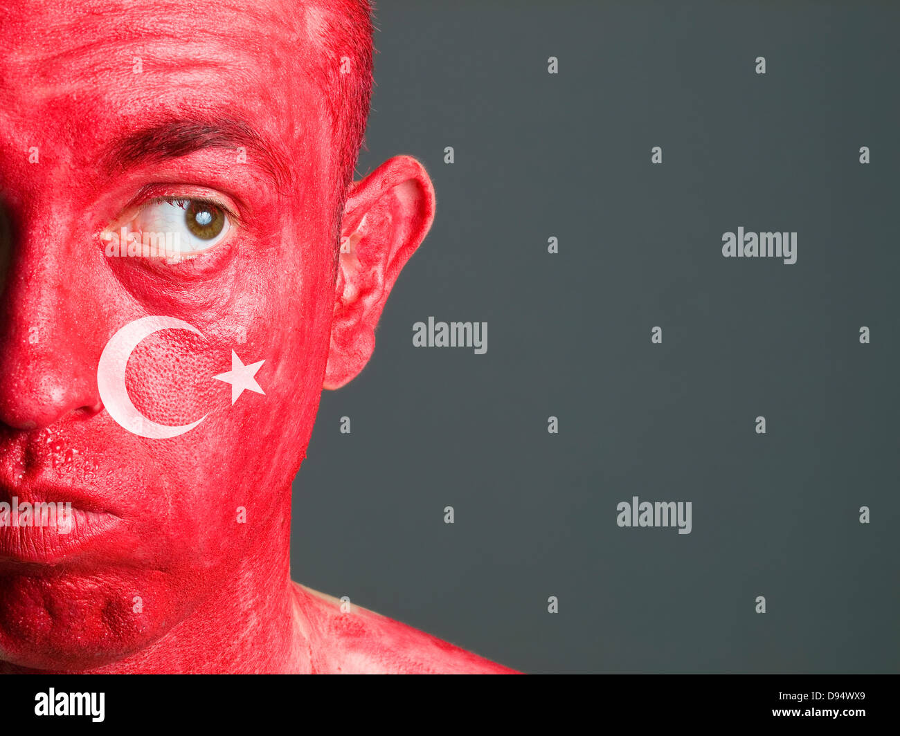Face man makeup with turkish flag and isolated on dark background - Stock Image
