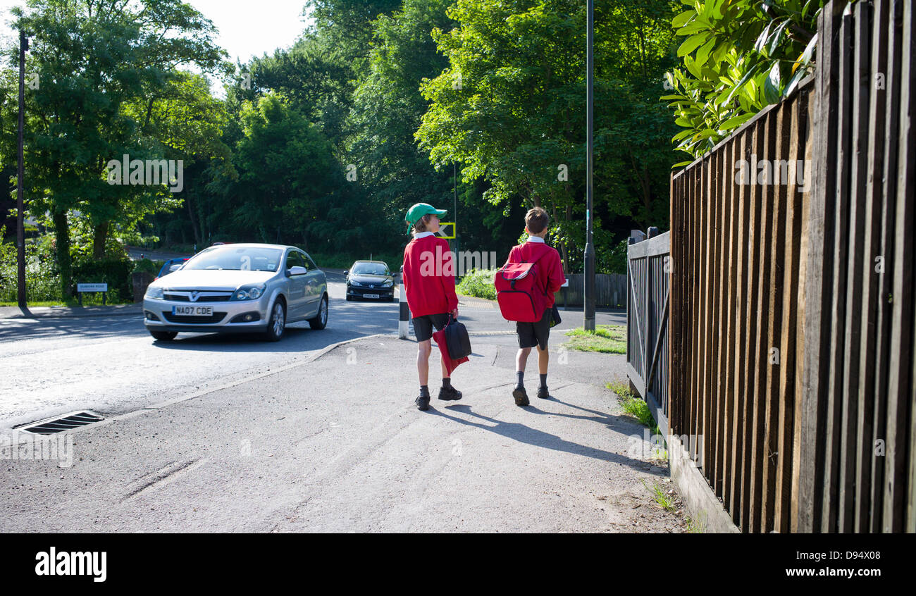 two young boys walk to school along busy road - Stock Image
