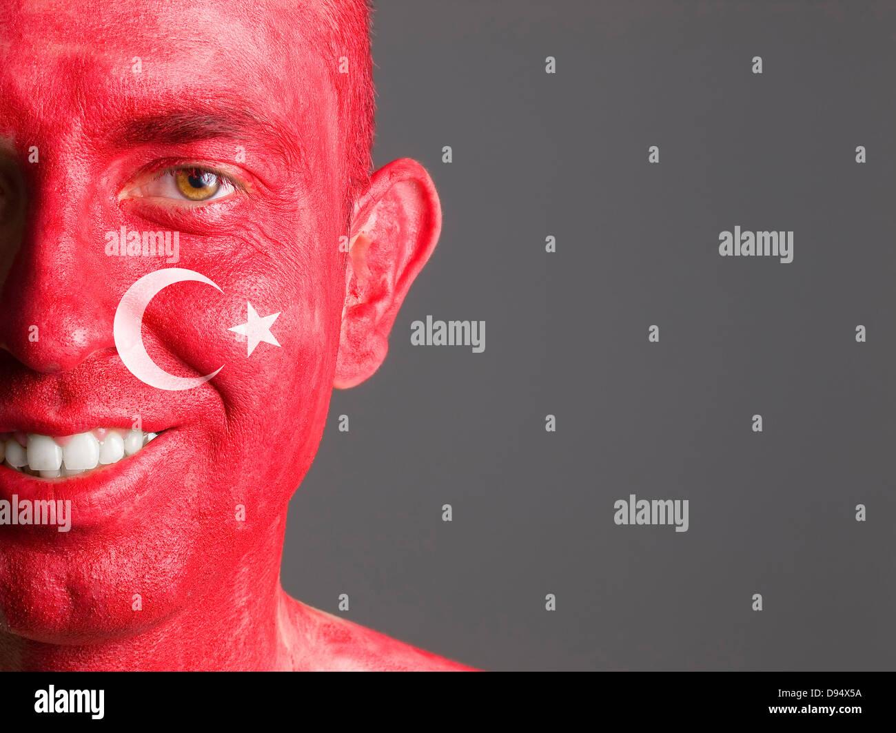 Face smiling man makeup turkish flag isolated on dark background - Stock Image