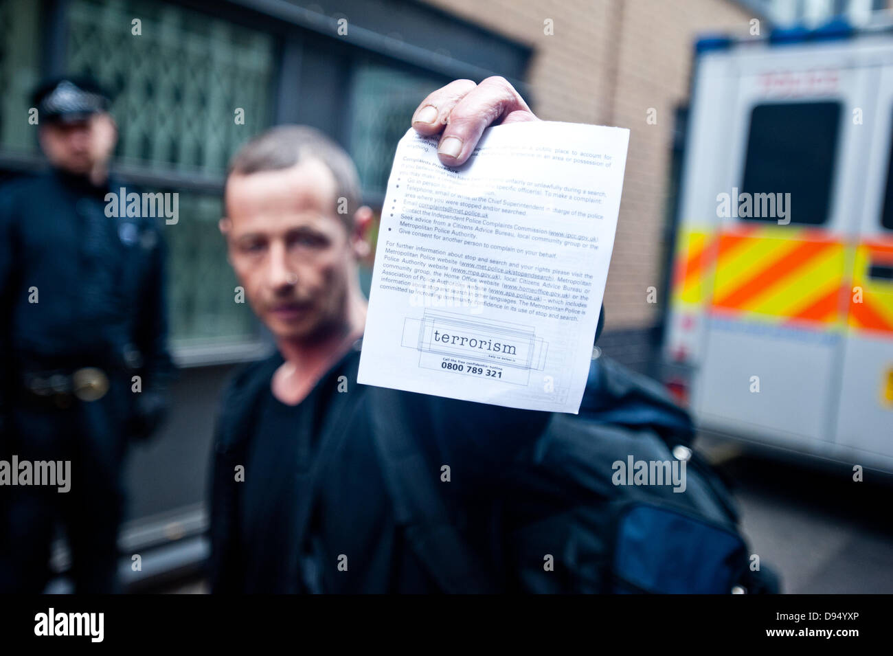 London, UK – 11 June 2013: a Stop G8 protester holds a 'Stop and search' notice for terrorism after being evicted - Stock Image