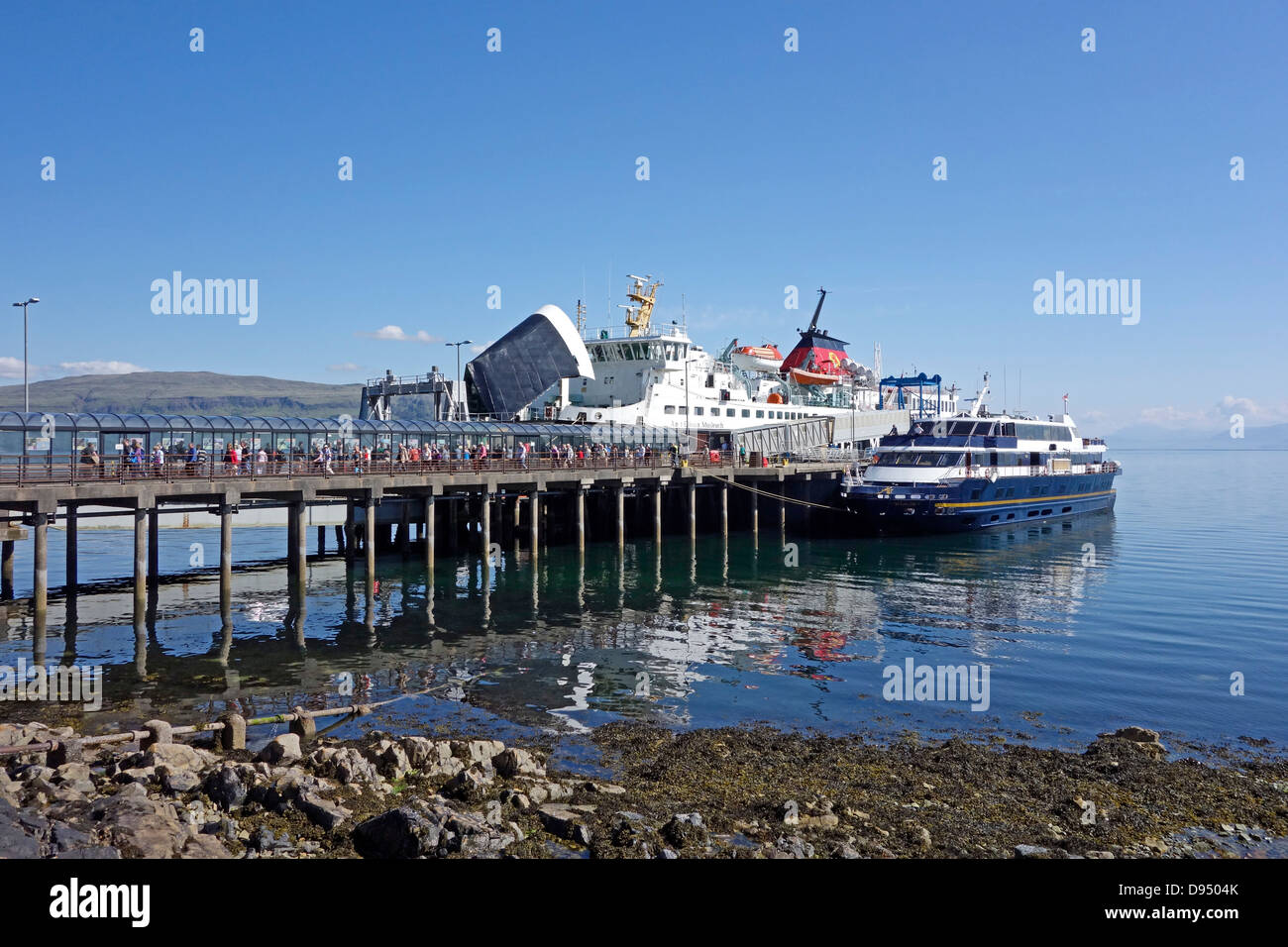 Cruise vessel Lord of the Glens moored at the pier in Craignure Mull while CalMac ferry Isle of Mull is discharging - Stock Image