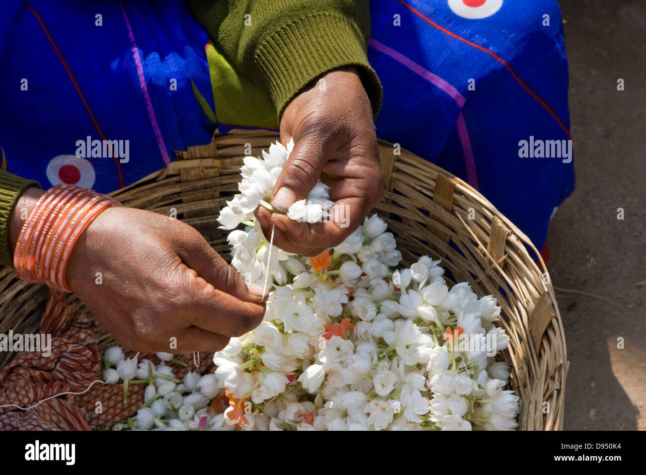 Asia, India, Karnataka, Belur, Woman making jasmine garlands outside a Hindu temple - Stock Image