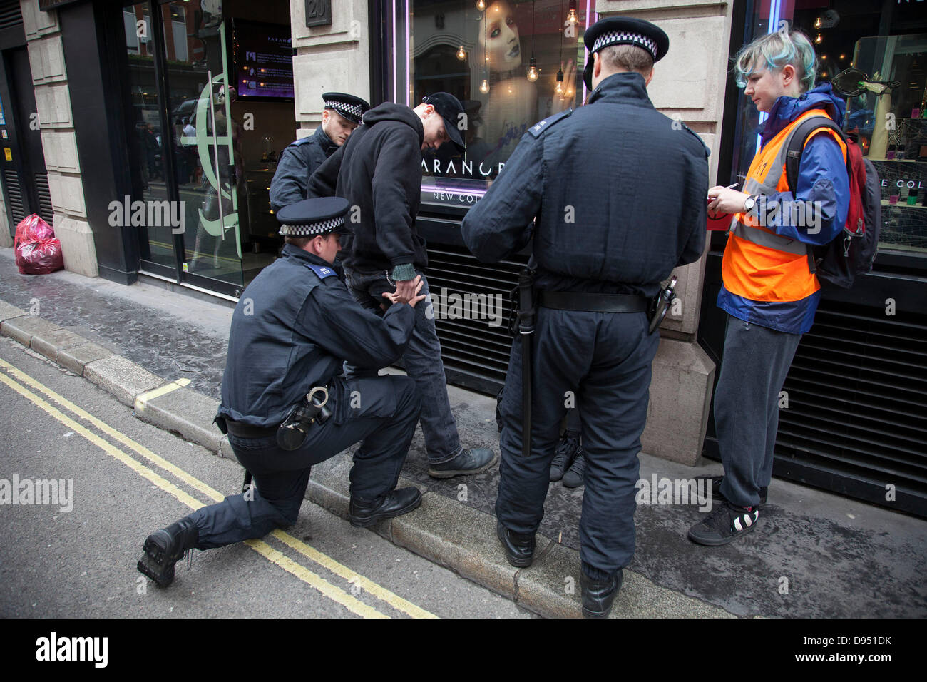 Protesters demonstrate against the upcoming G8 summit in central London, UK. Protesters being stopped and searched - Stock Image