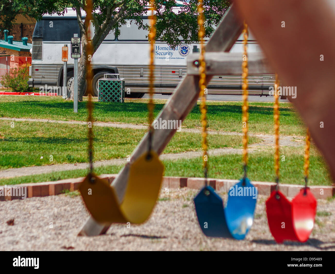 Homeland Security bus parked behind playground - Stock Image
