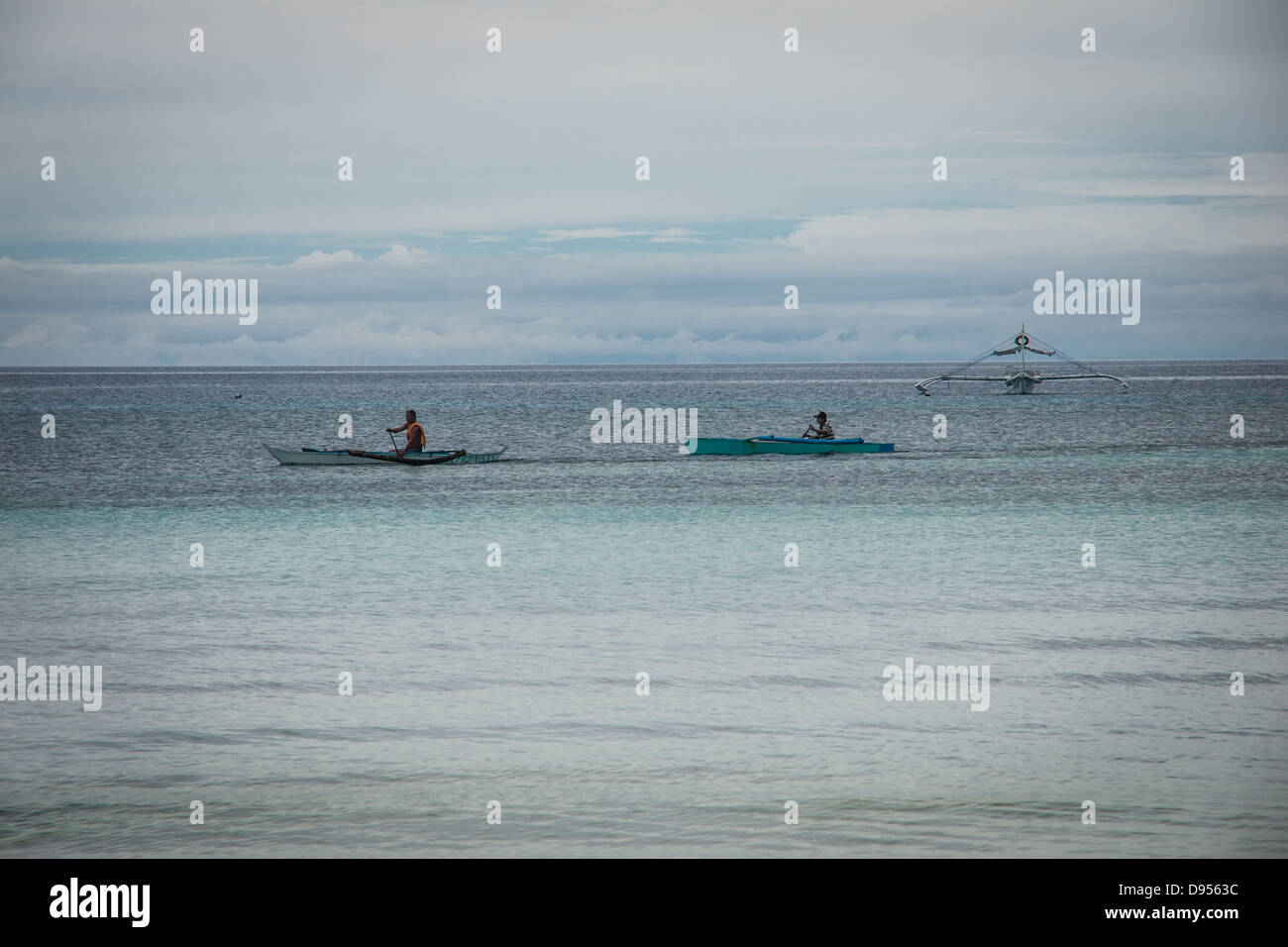 Two Filipinos paddling away in traditional outrigger boats on Dumaluan Beach on island of Bohol in Central Visayas, - Stock Image