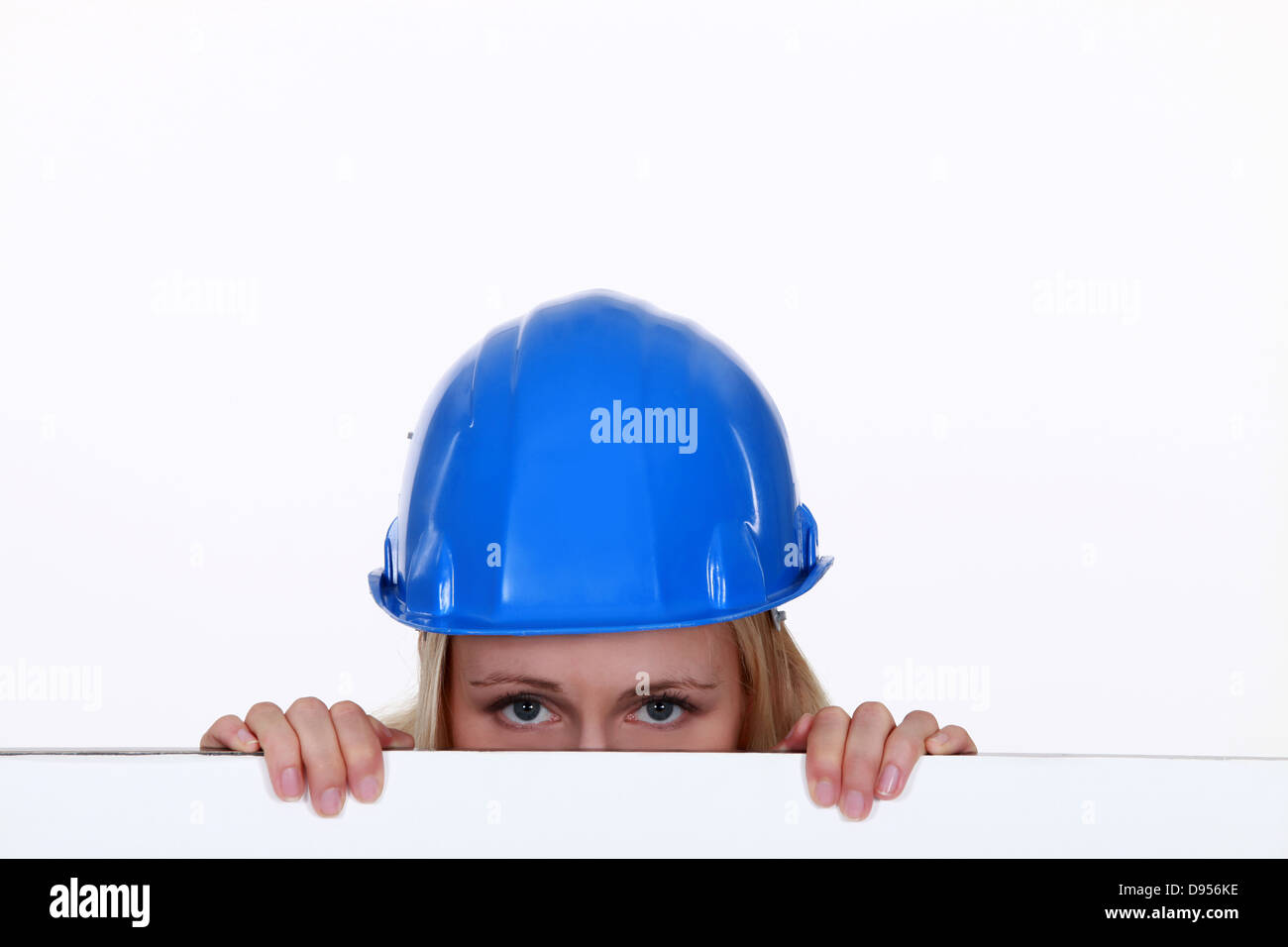 Tradeswoman peering over a low wall - Stock Image