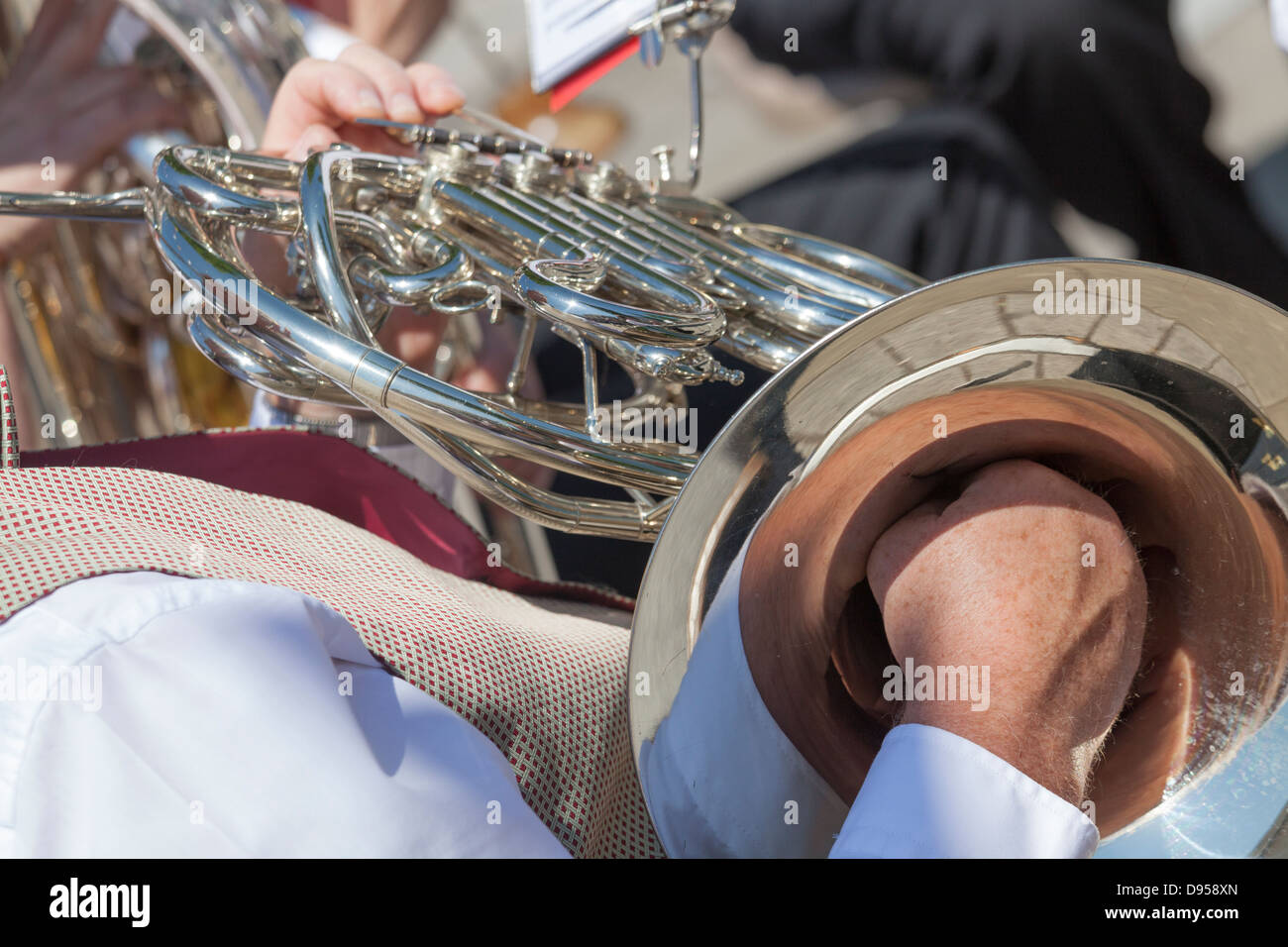 close of male playing french horn and hand muting - Stock Image