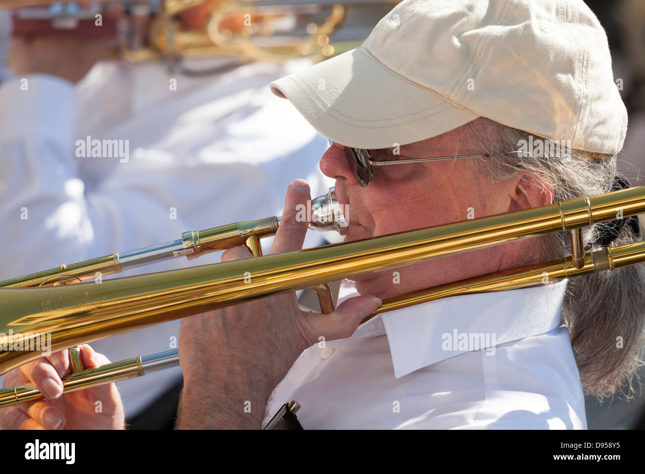 close up of male trombone player in baseball cap and pony tail - Stock Image
