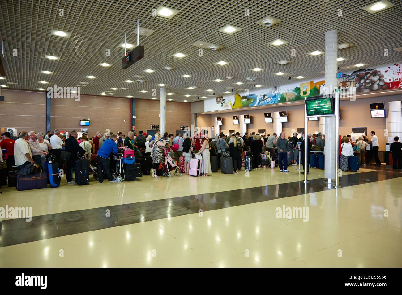 tourists queuing at check in desks at reus airport catalonia spain - Stock Image