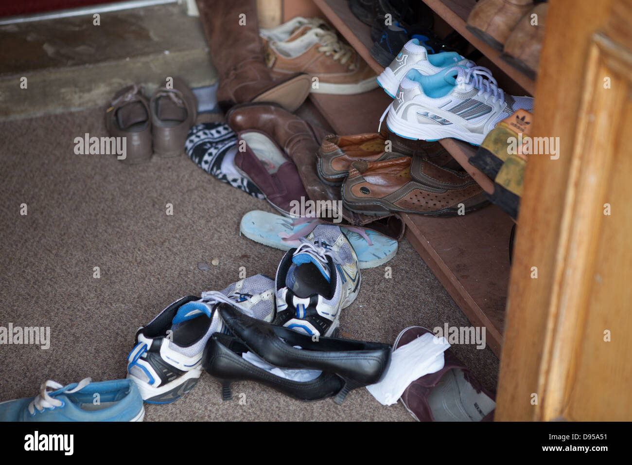 A varied collection of shoes and trainers outside a Thai Temple in the UK. - Stock Image