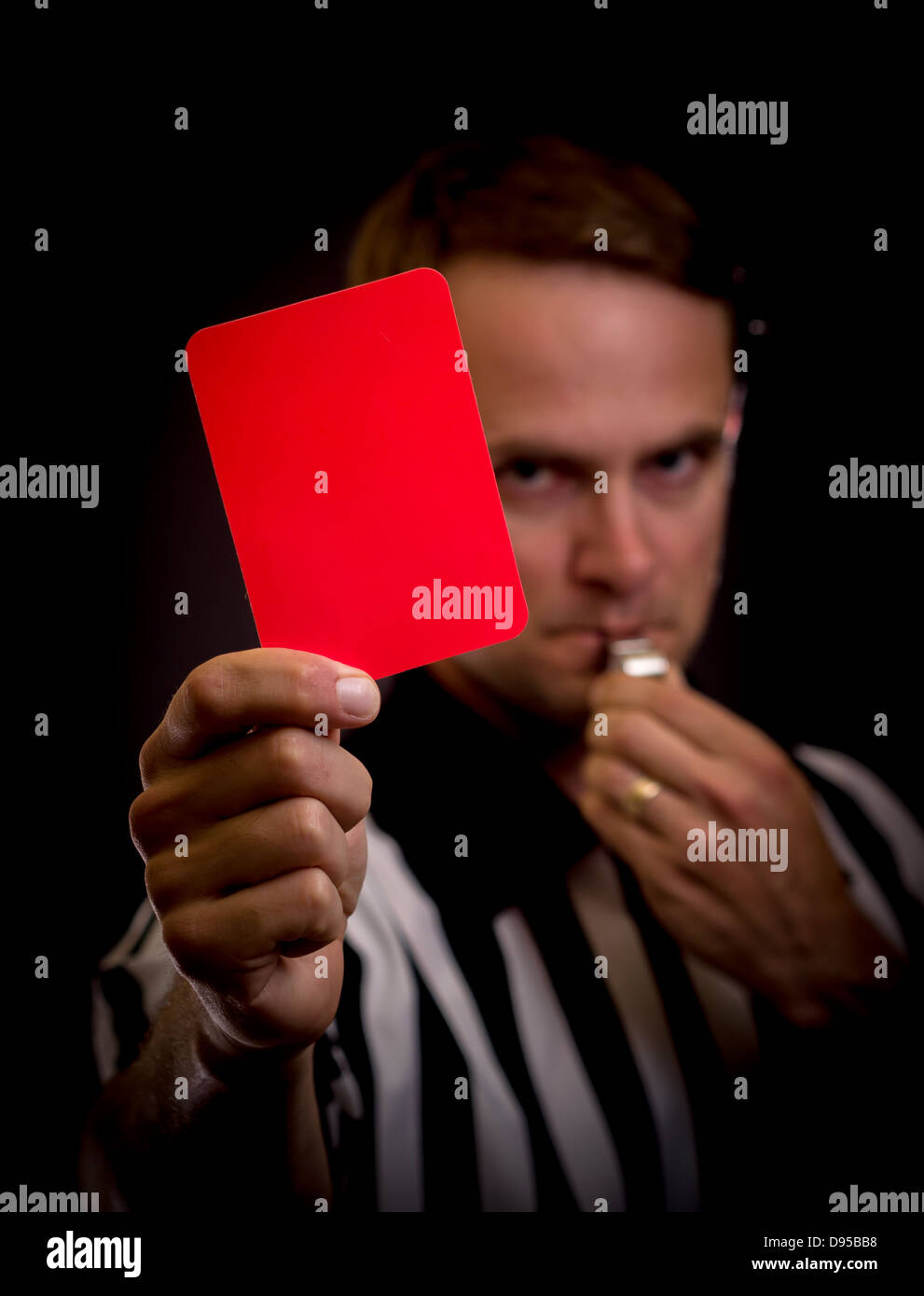 Referee holding red card for foul concept - Stock Image