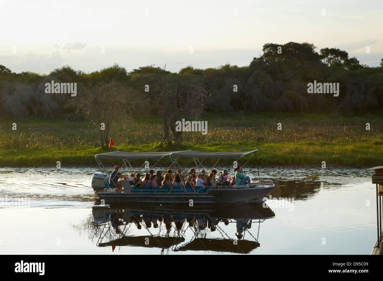 Tourist boat on Thamalakane River by Okavango River Lodge, Maun, Okavango Delta, Botswana, Africa - Stock Image