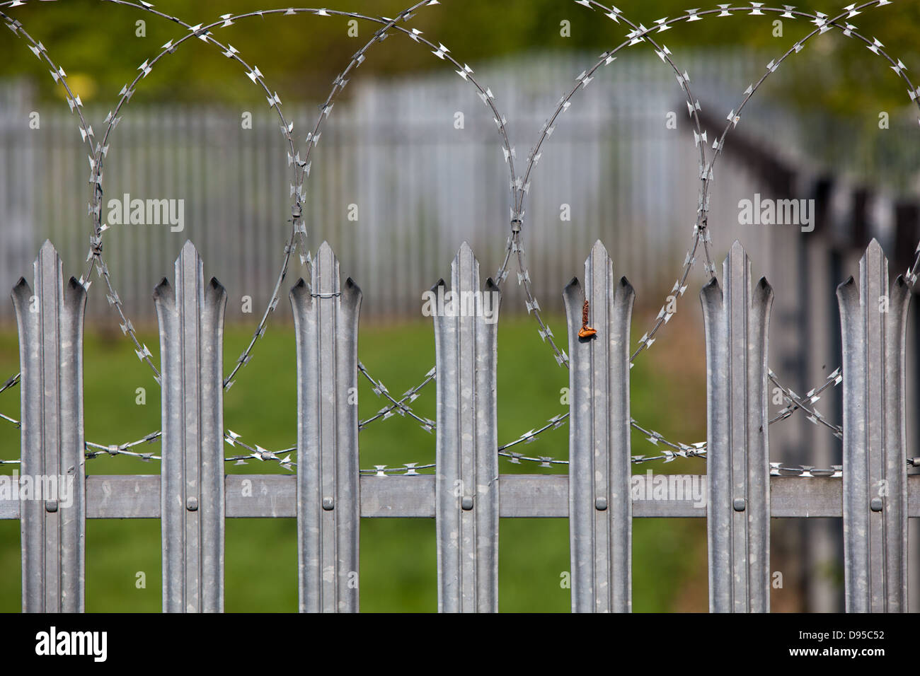 Spiked metal railings and razor wire around a secure compound. - Stock Image