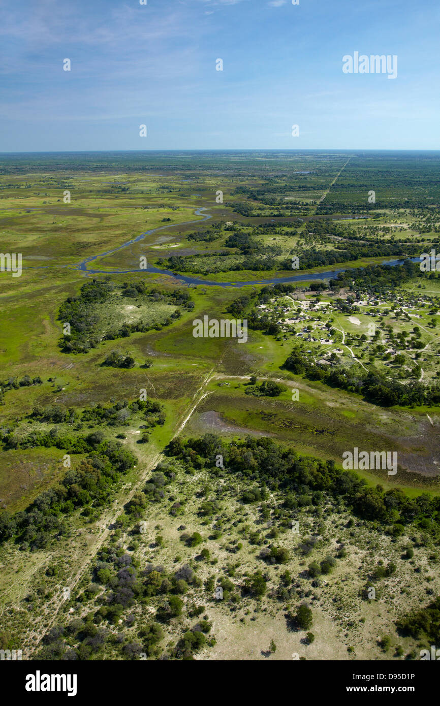 Buffalo fence (disease control fence) separating wildlife from domestic cattle, and Boro River, Okavango Delta, - Stock Image