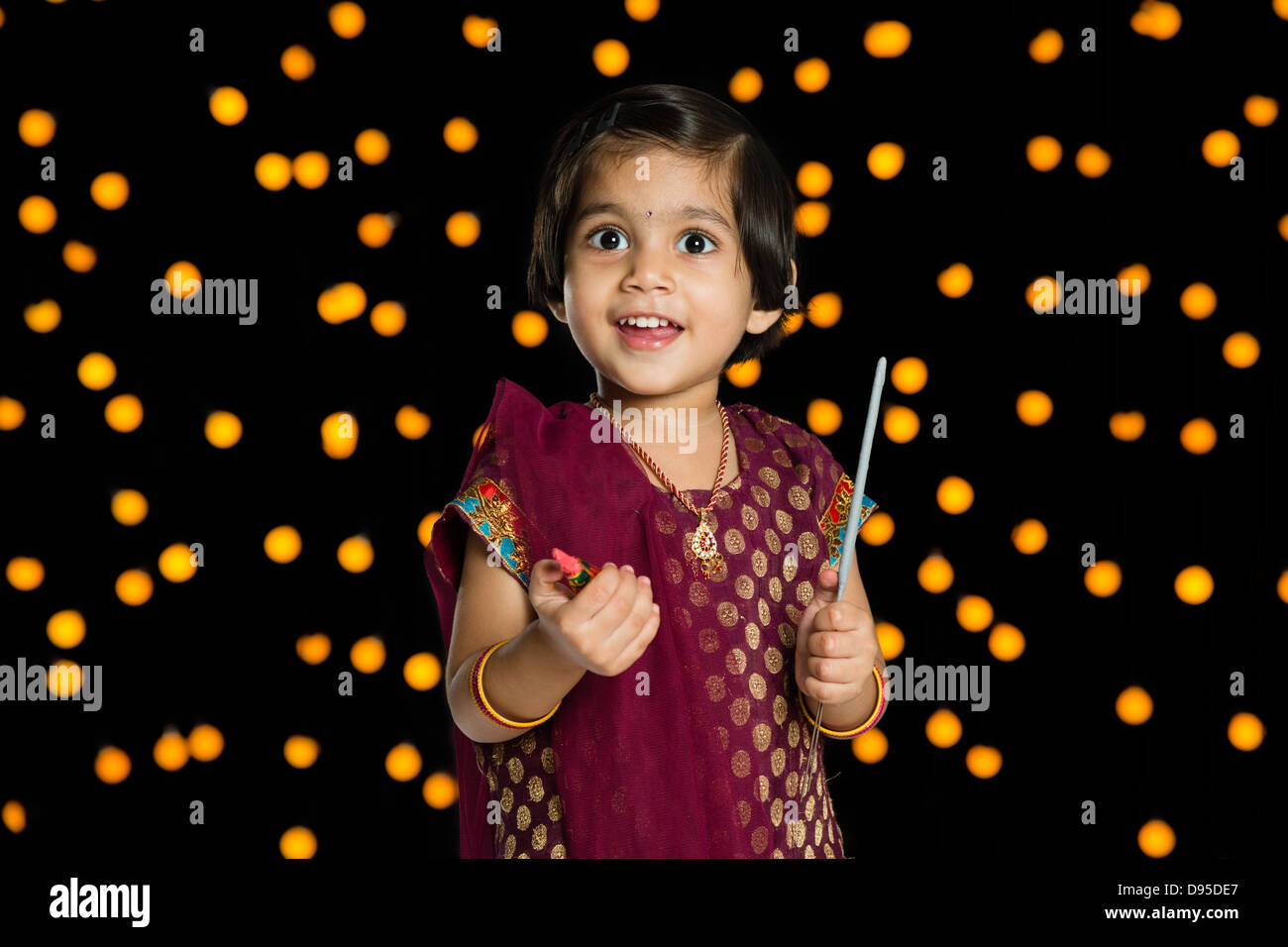 Girl holding fire crackers and smiling in front of Diwali decoration Stock Photo