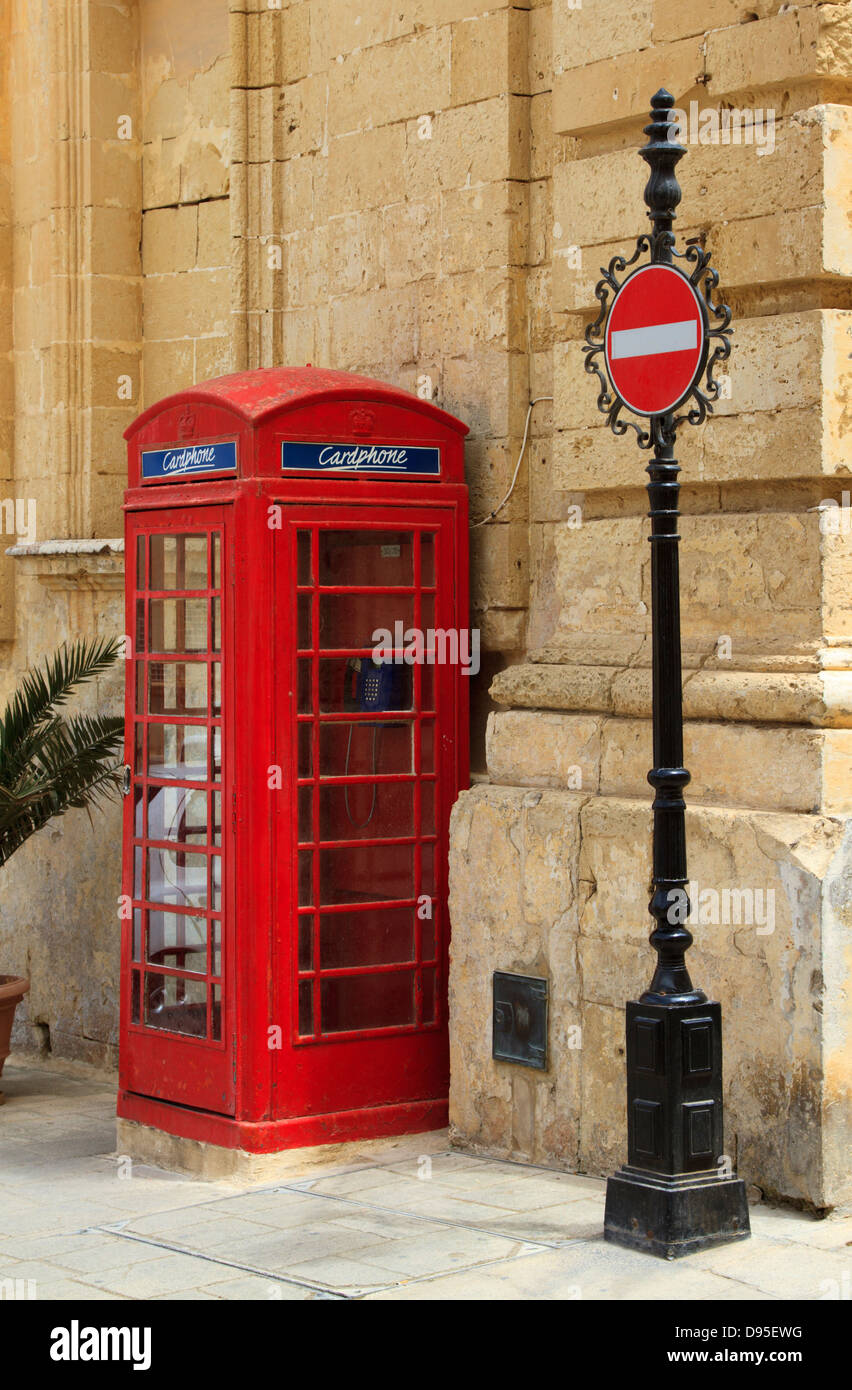 Red telephone kiosk and decorative no entry sign in Pjazza San Pawl, St Paul Square, Mdina Malta - Stock Image