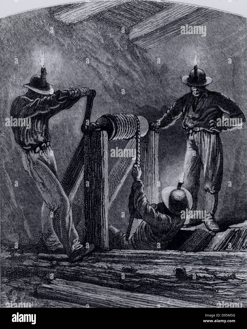 A Cornish winze shaft, used for exploration.  A man attached to a rope is being lowered down the shaft by a simple - Stock Image