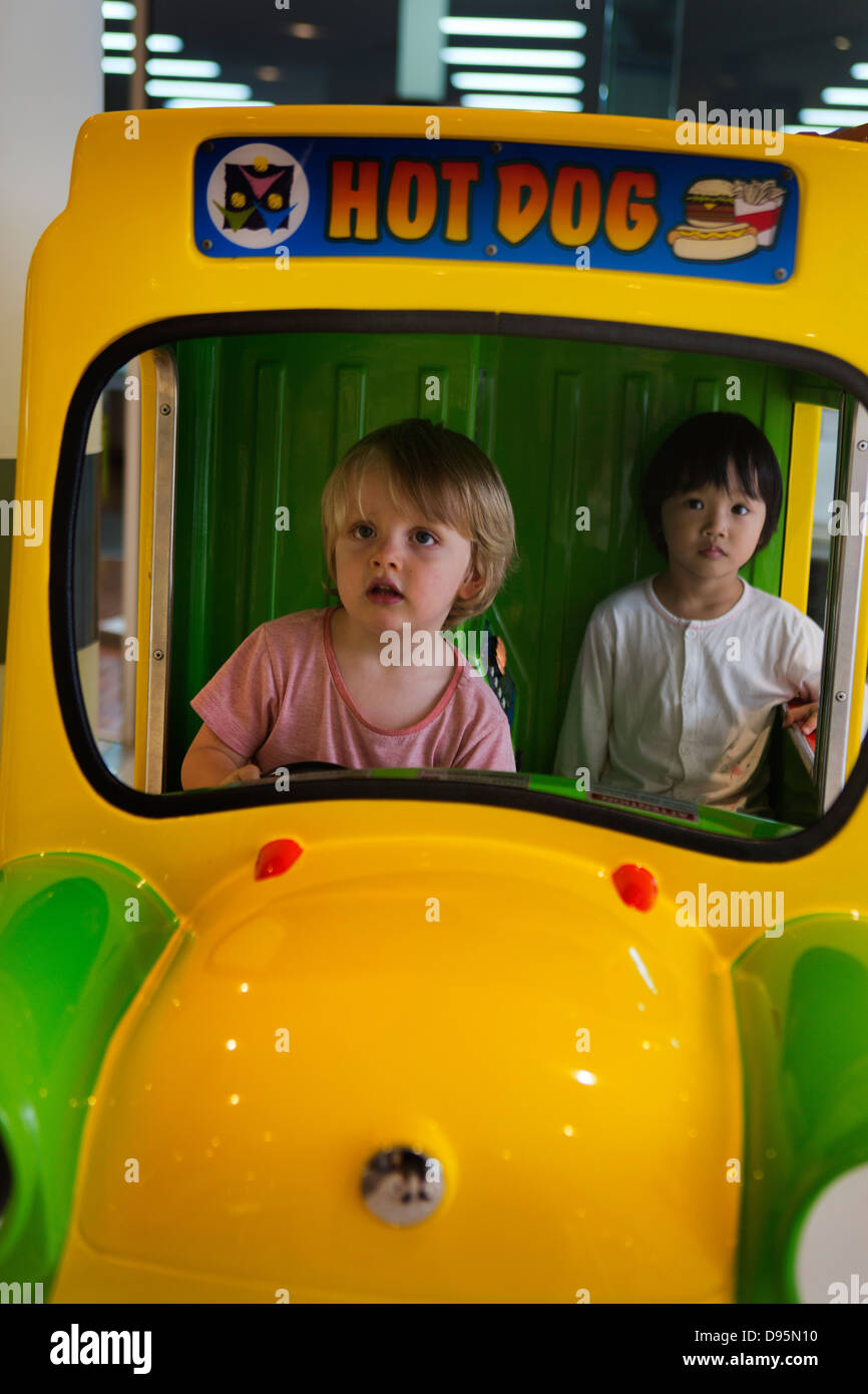 3 year old boy drives a play hot dog truck with a 3 year old girl as passenger in shopping mall, Sydney, Australia - Stock Image