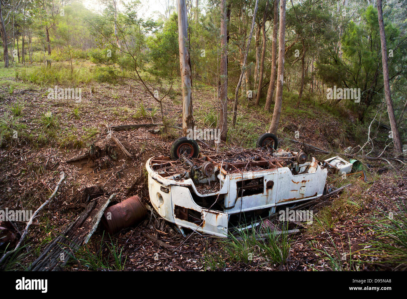 Abandoned white rusting camper van wreck in a wood in the Australian bush - Stock Image