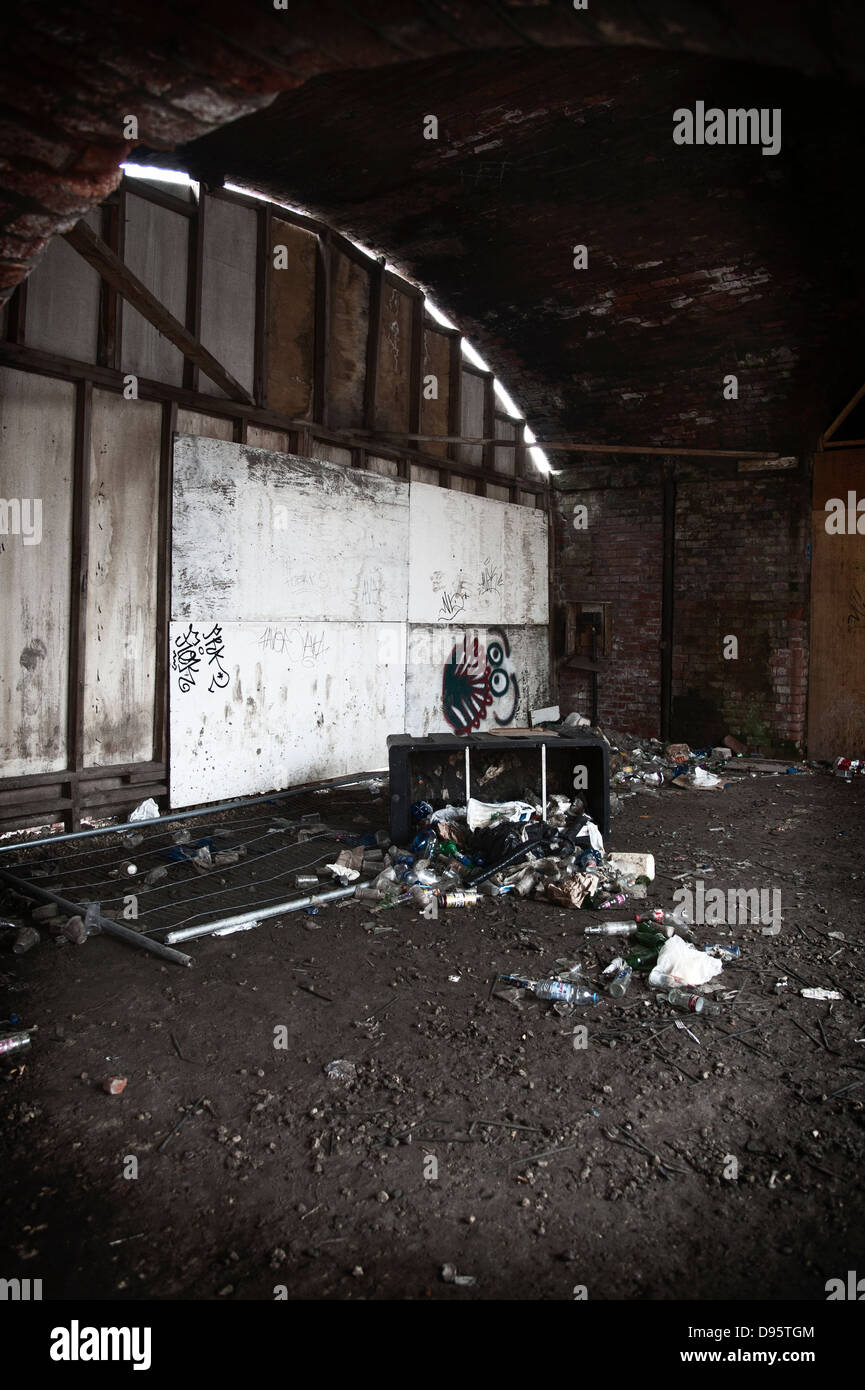 Rubbish dumped under a railway bridge in this image showing urban decay. - Stock Image