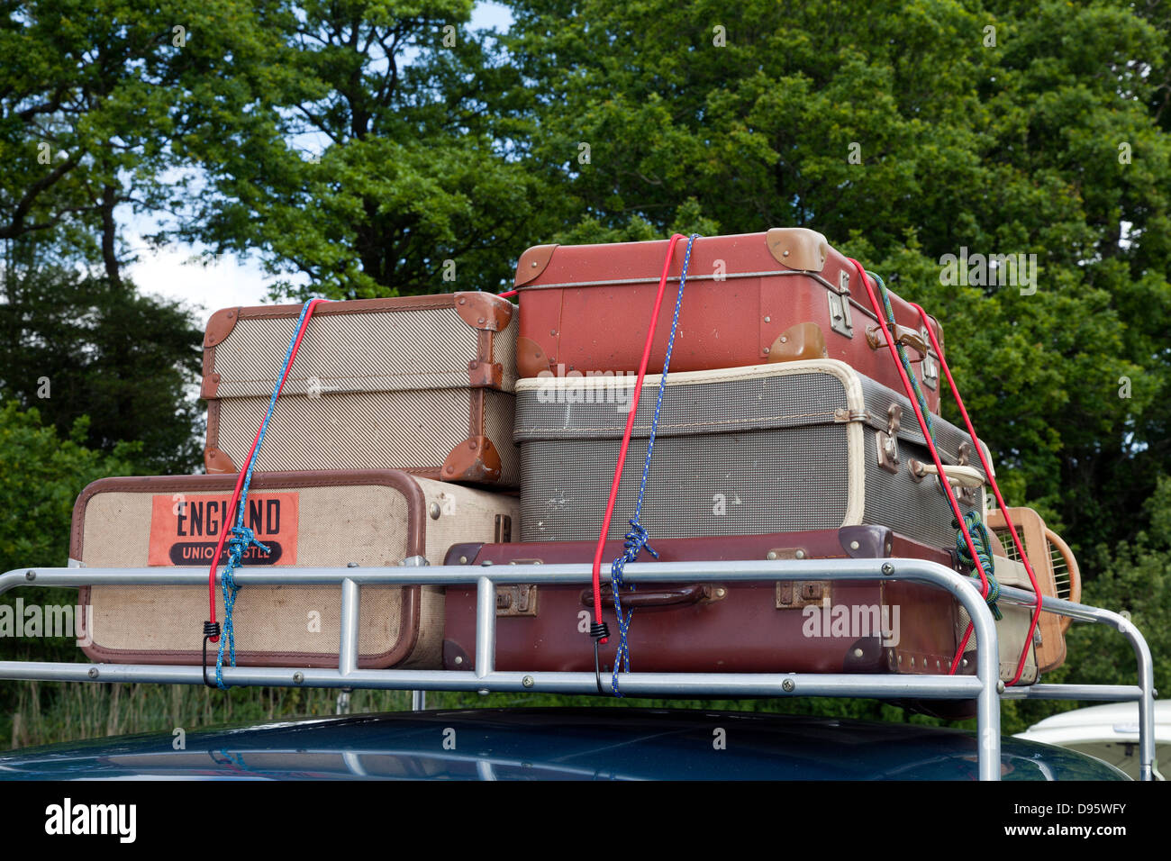 Old style fashioned luggage suitcases on car roof rack - Stock Image