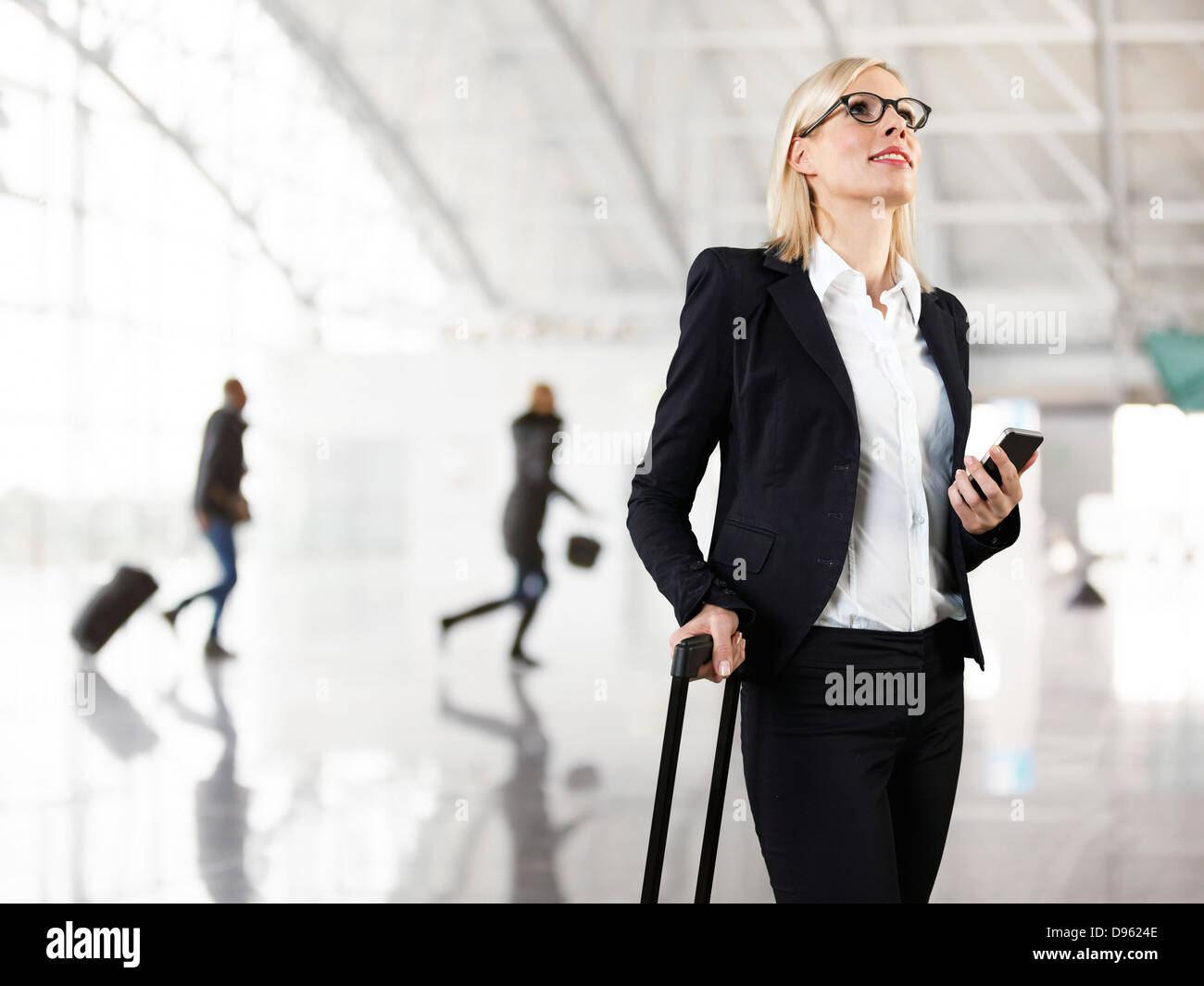 Businesswoman holding briefcase and mobile phone, smiling - Stock Image