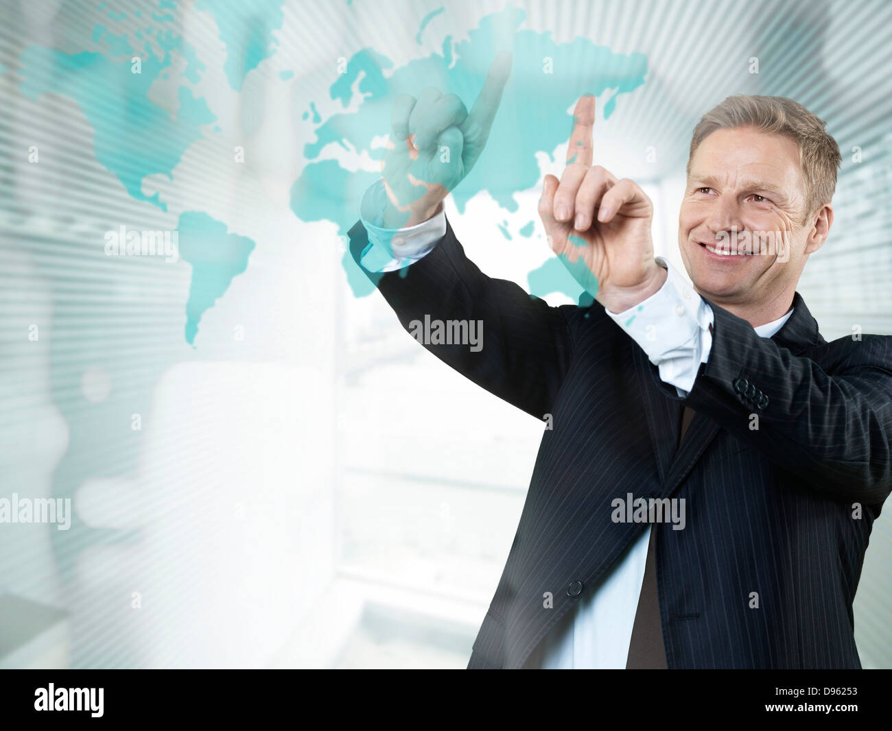 Businessman giving presentation in office, smiling - Stock Image