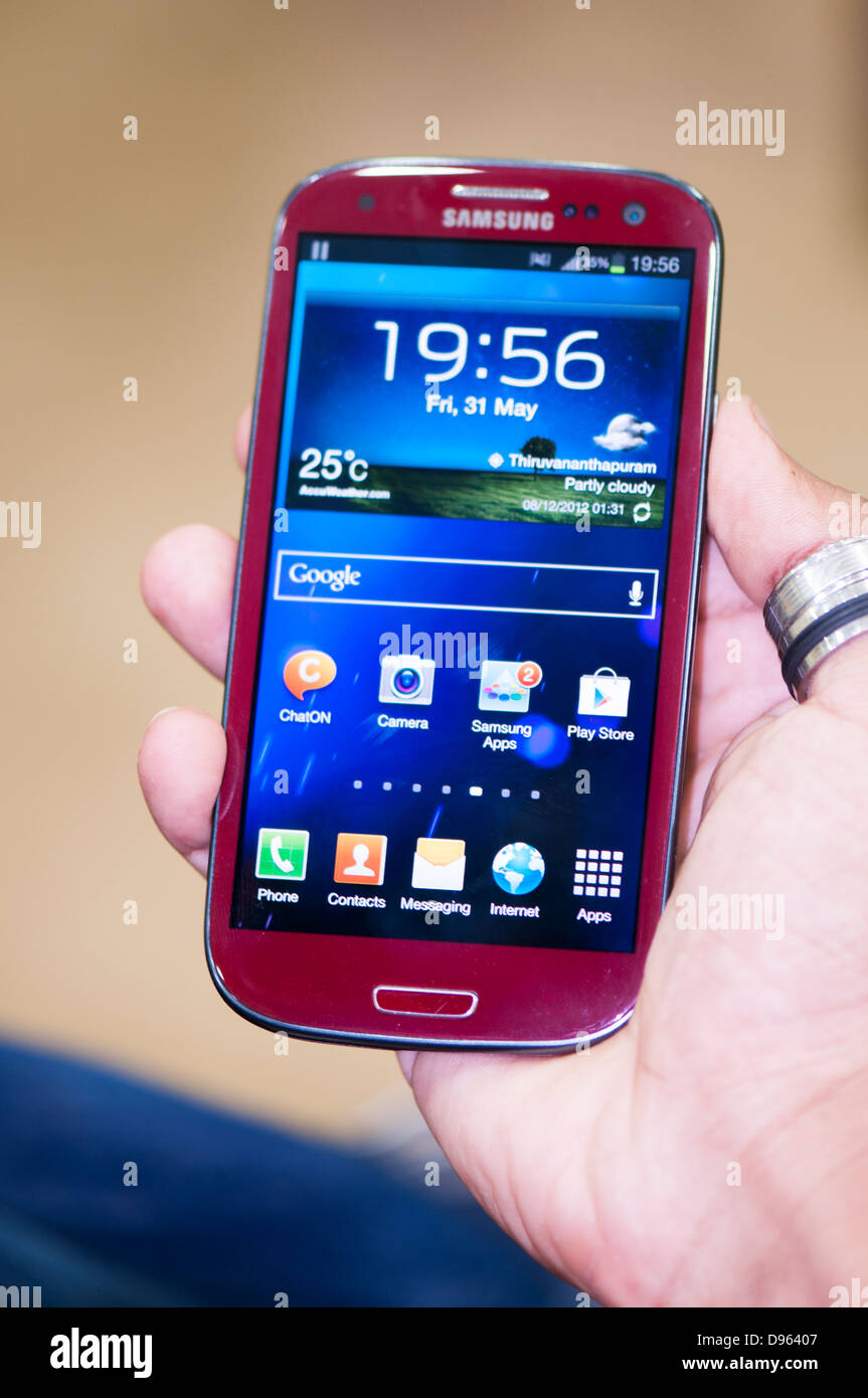 Hand holding Samsung S3 smartphone, close up - Stock Image
