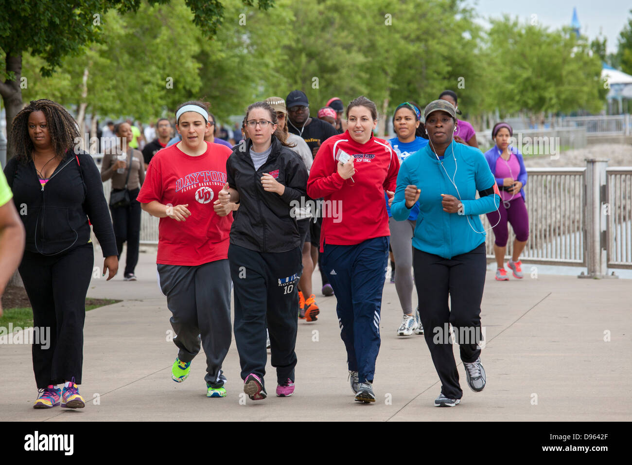 Young professionals gather along the Detroit Riverwalk for exercise and networking. - Stock Image