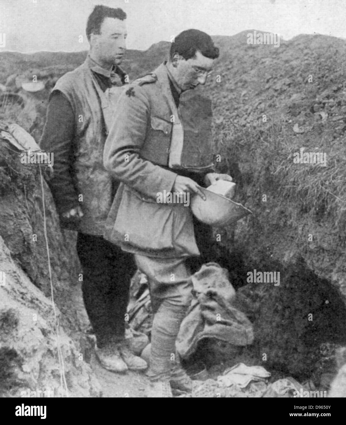 World War I: Chaplain of the British regiment the lst Munsters saying a burial prayer over soldiers killed in their - Stock Image