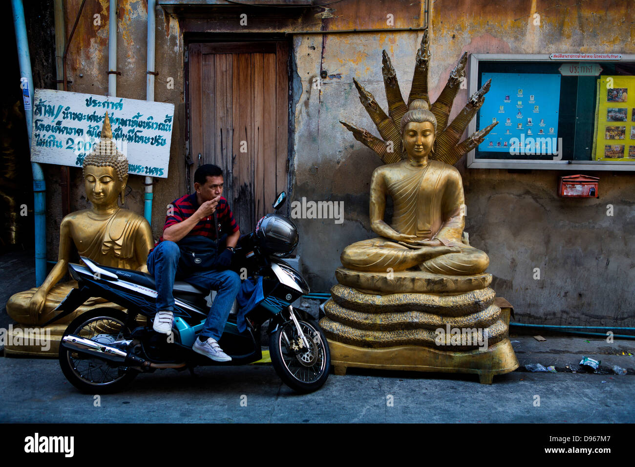 Man resting on motorbike in the area of Bangkok making Buddhist and Hindu icons - Stock Image