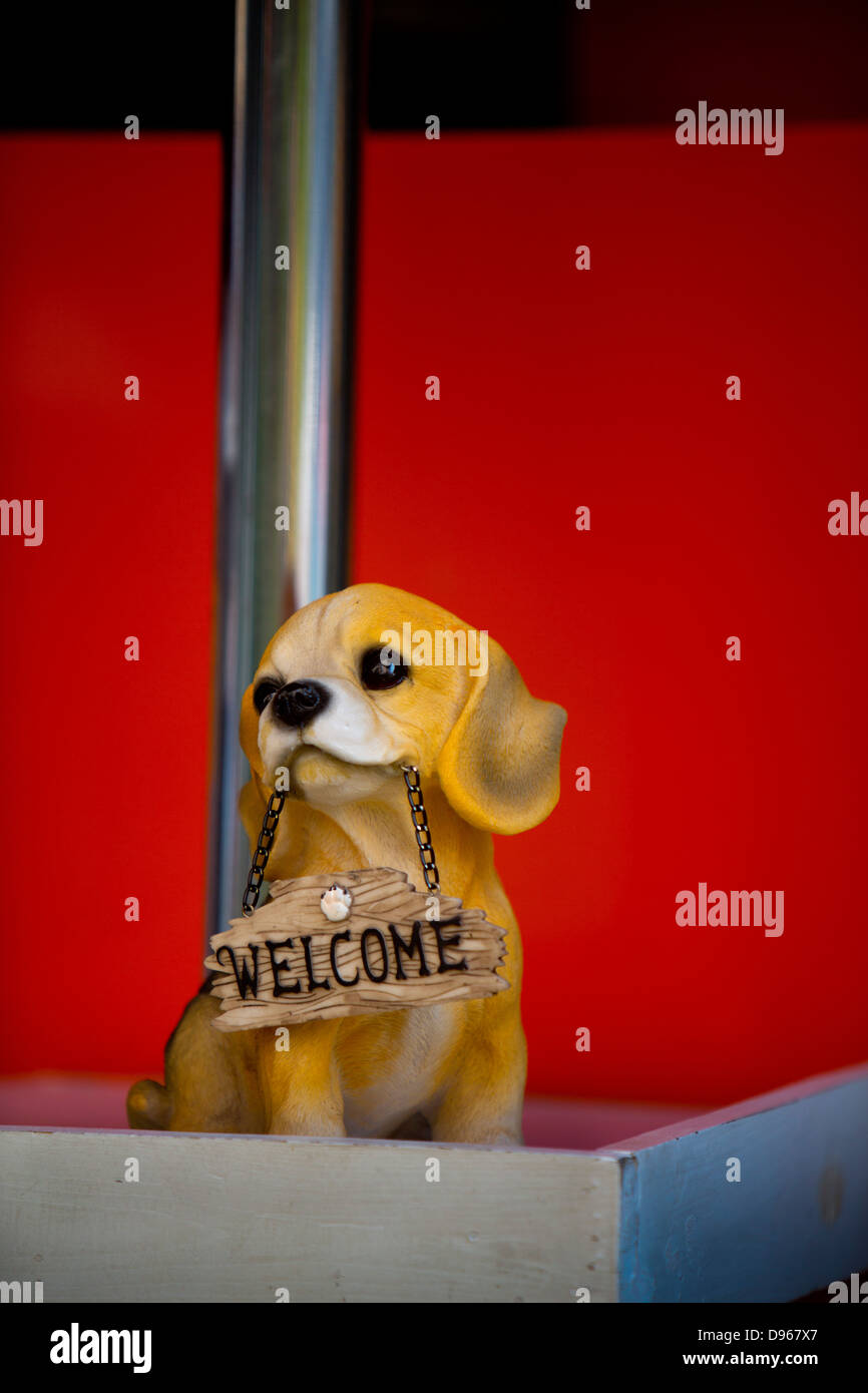 Plastic dog bearing a Welcome sign on street in Bangkok - Stock Image