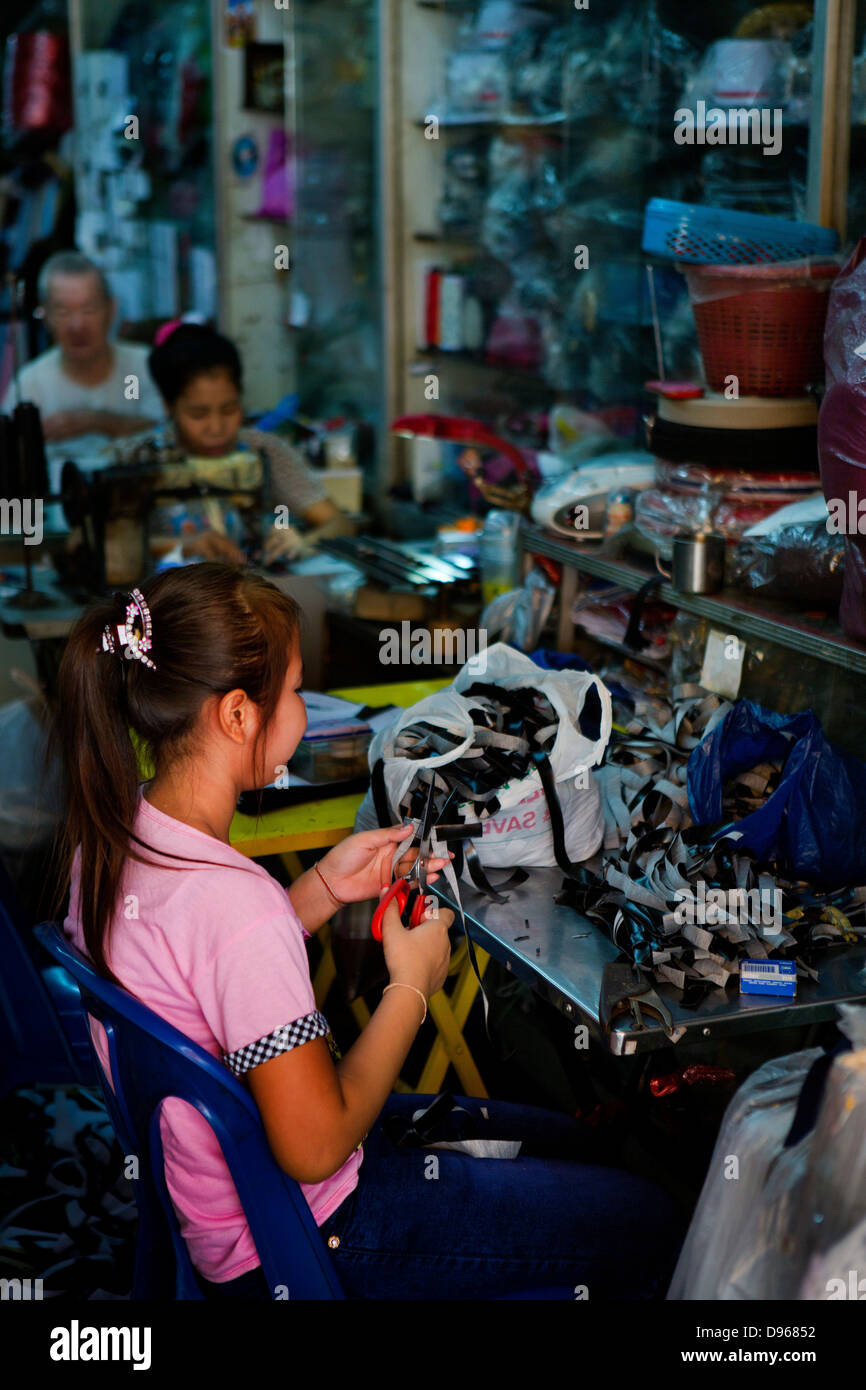 Family workshop with adults on sewing machines and young girl cutting fabric in Bangkok, Thailand - Stock Image
