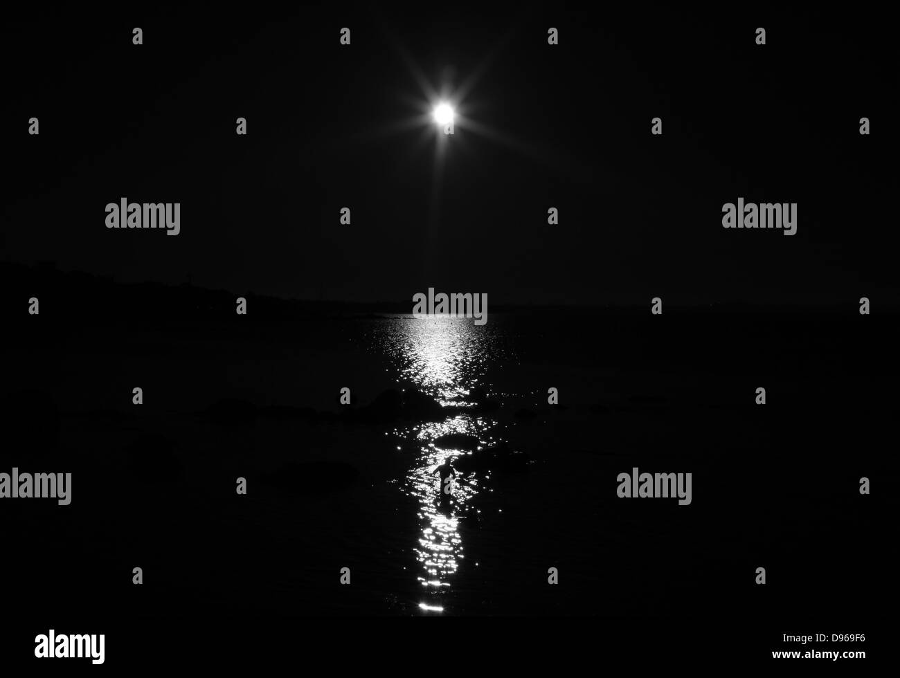 The figure of a man standing in the sea silhouetted by a bright sun. - Stock Image