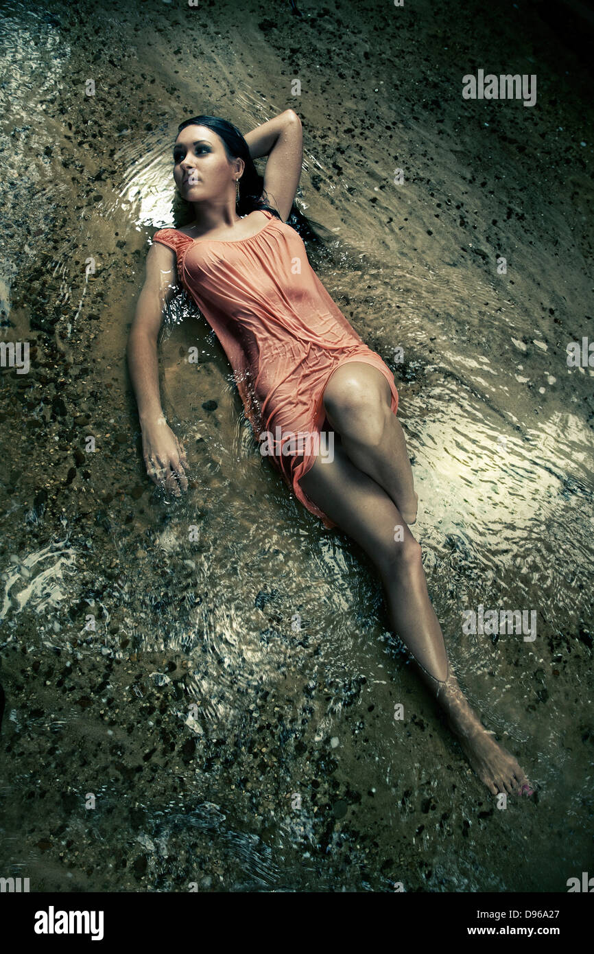Woman laying in wet dress in creek bed - Stock Image