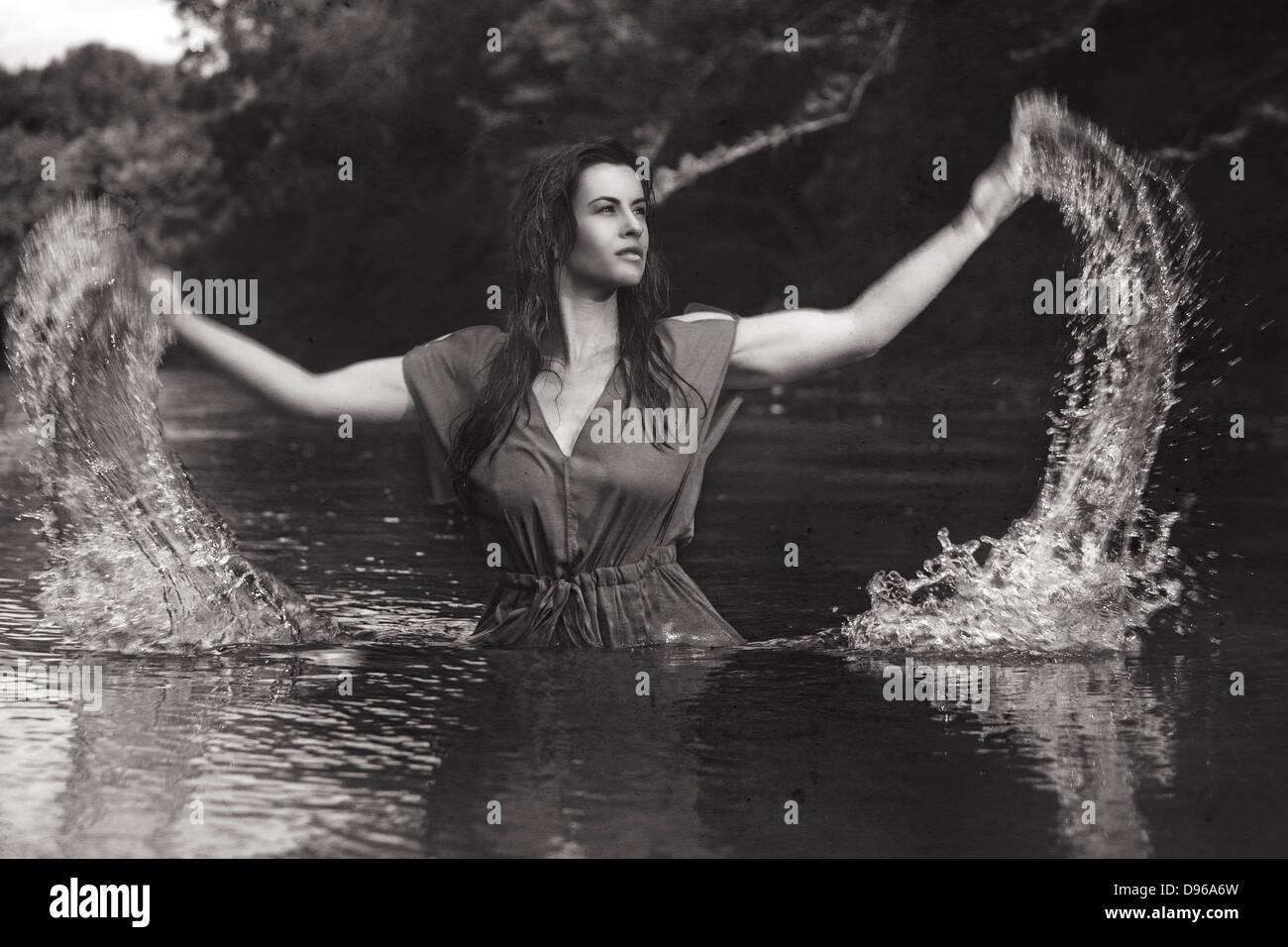 Woman splashing water out of river - Stock Image