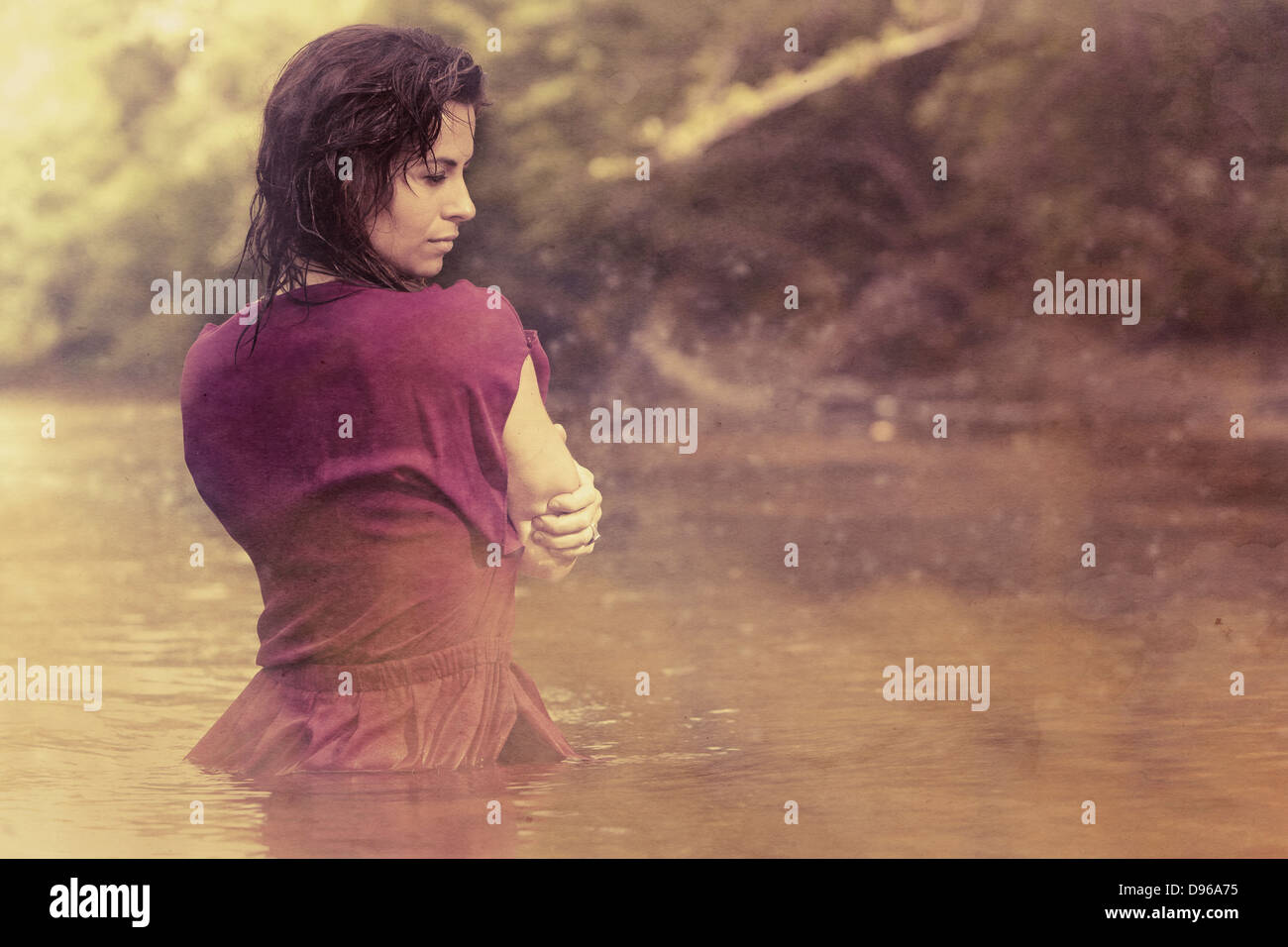 Woman in dress standing in mist covered water - Stock Image
